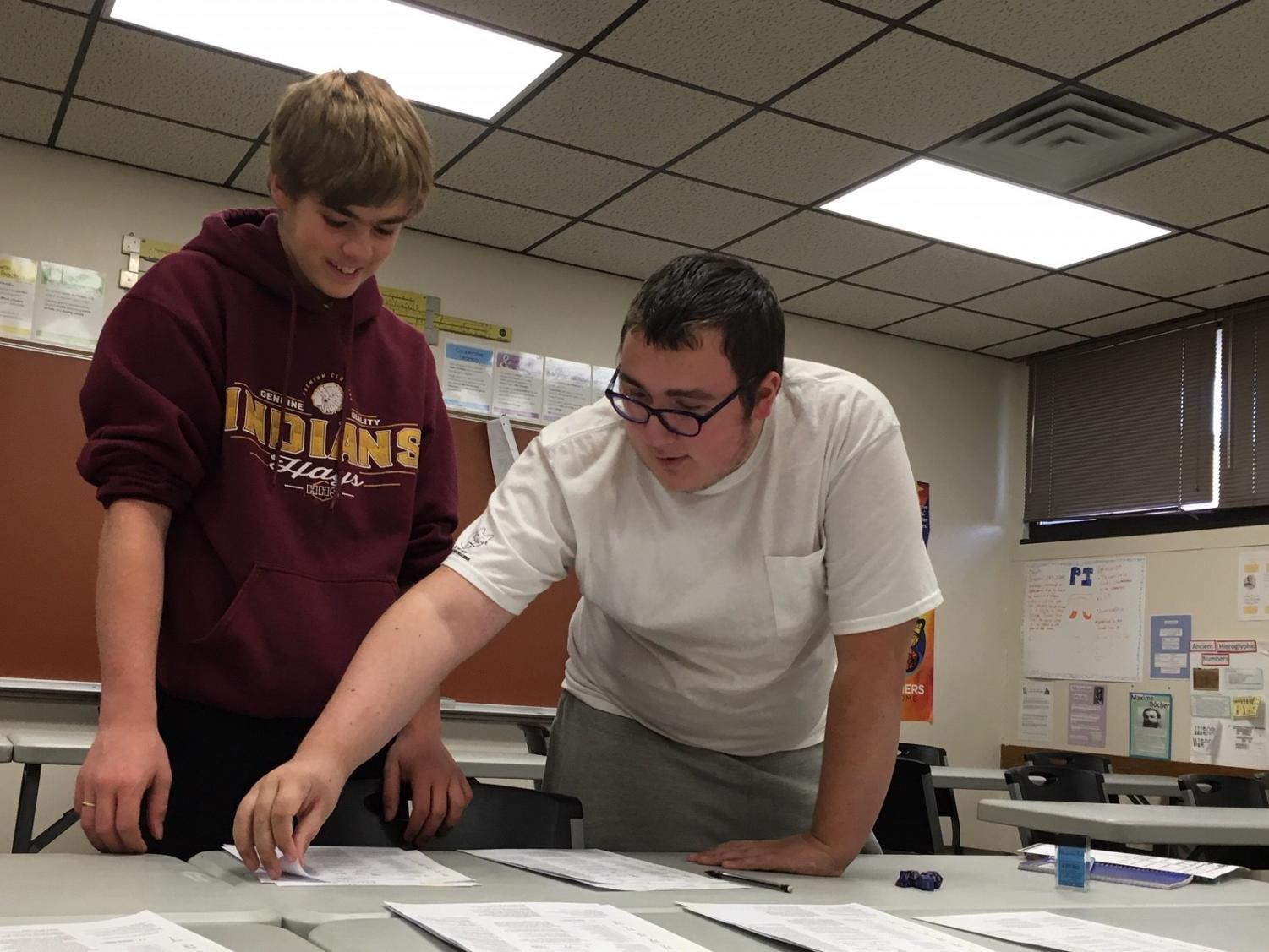 Juniors John Garner (left) and John Rupe (Right) look over character sheets during the Dungeons and Dragons meeting. The club met for the first time after school on Oct. 21 in room 121. Approximately 12 students attended the meeting.