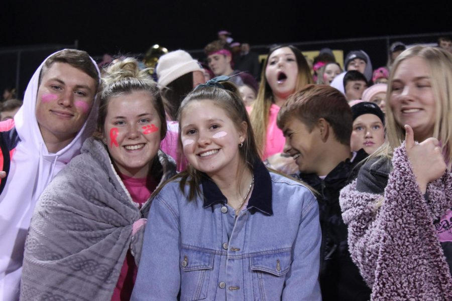 Seniors+Tucker+Johnson%2C+Brooklin+Robben%2C+Cassidy+Prough%2C+and+Sierra+Bryant+cheer+on+the+football+team+during+the+game+on+Oct.+25.+The+theme+for+the+night+was+pink+out+to+support+breast+cancer+awareness.+