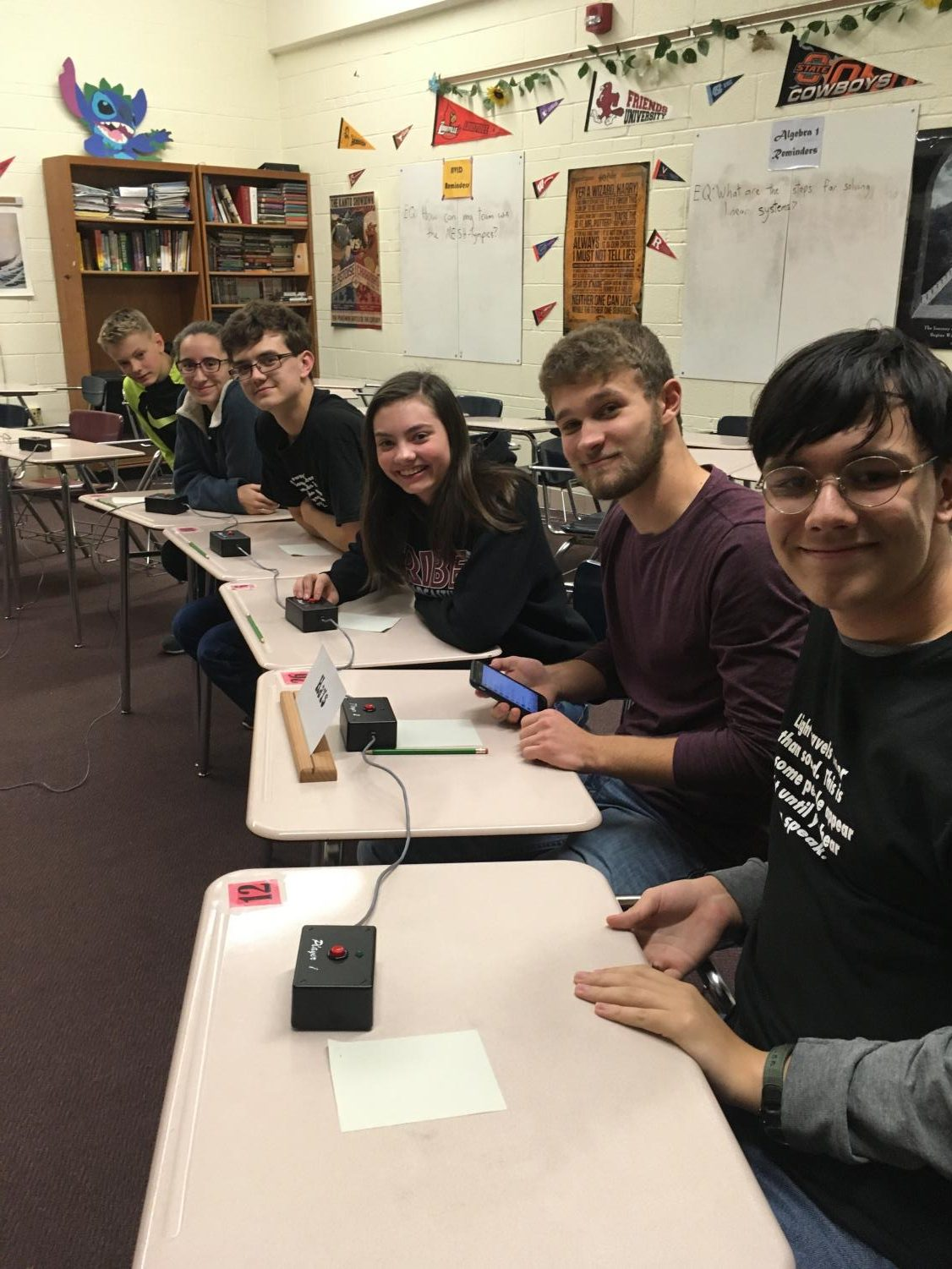 Varsity Scholars Bowl sits at desks with buzzers during the meet on Nov. 21. The team made it to semifinals, falling to Salina South.