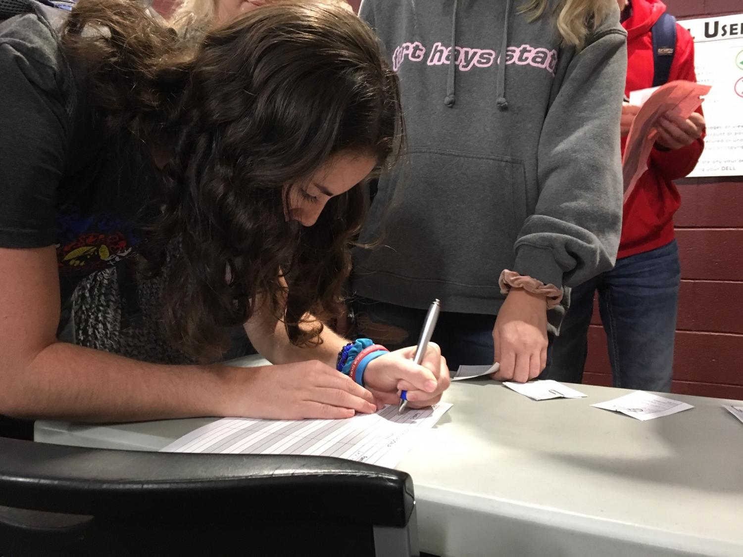 Junior Sophia Garrison signs up to bring groceries for the Holiday Help Project during the NHS meeting on Nov. 25. Groceries need to be turned in my Dec. 6.