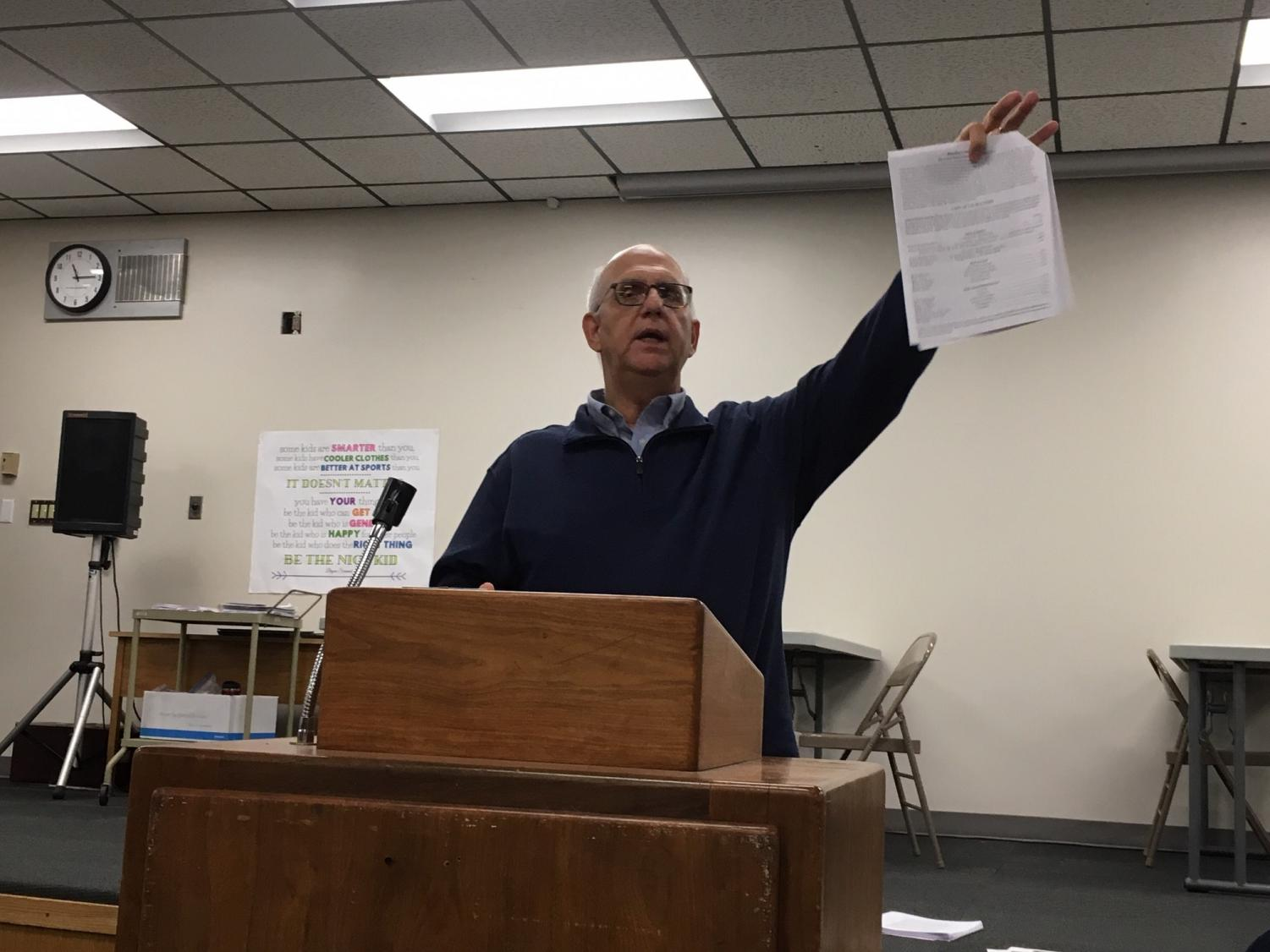 Director Bill Gasper holds up the informational packet that was passed out during the meeting. The packet contains information about auditions as well as the participation agreement that must be turned in to the office by Dec. 4.