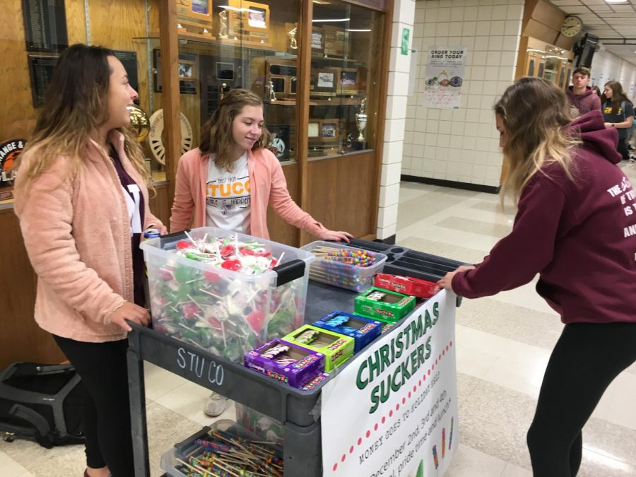 StuCo president Maddie lohmeyer tapes a sign on the candy cart before school on Dec. 2. StuCo will be selling candy Dec. 2, 3 and 4 before school, during PRIDE Time and during lunch. All proceeds will go toward the Holiday Help Project.