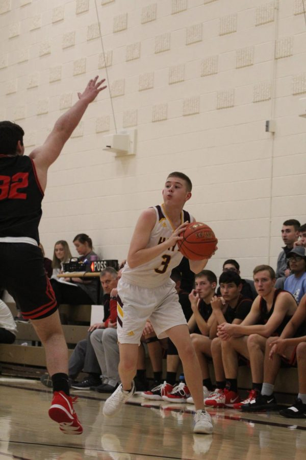 Sophomore Wesley Oakley looks for an open teammate to pass to during the home game against Great Bend on Jan. 14.