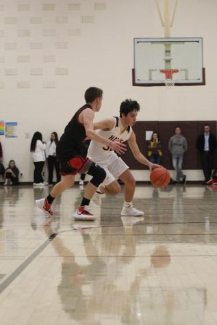 Sophomore Ashton Hernandez dribbles the ball around an opponent during the home game against Great Bend on Jan. 14.