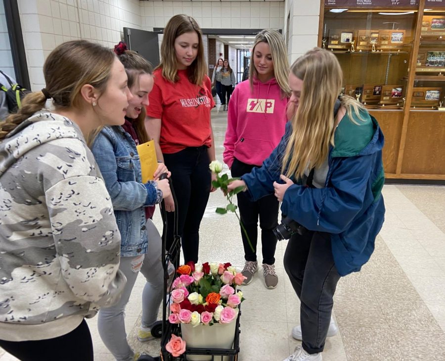 Members of Foreign Language Honor Society sell a rose to senior Emma Pfannenstiel on Feb. 13.  This was the society's second year selling roses for Valentine's Day.