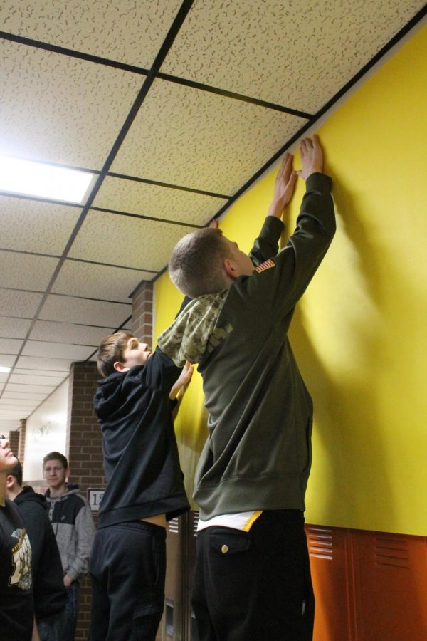The sophomores hang up a yellow poster in their hallway for the decorating competition.