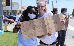 Senior Alicia Phlieger (left) and junior Aleyia Ruder (right) hold a sign during the protest on May 31.