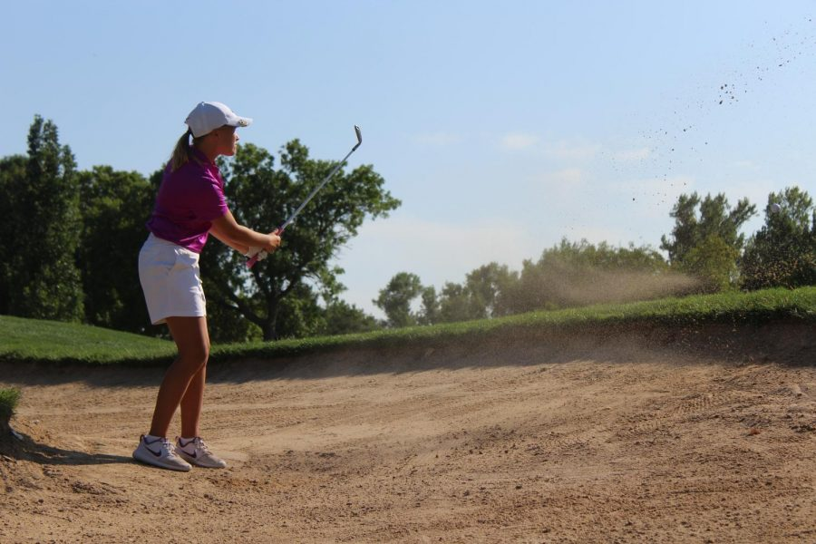 Varsity member Abbie Norris shoots out of the sand and on to the green at Smoky Hill Country Club.