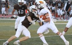 Junior quarterback/ running back Dylan Drieling stiff arms a Buffalo in game on September 25th in Garden City.