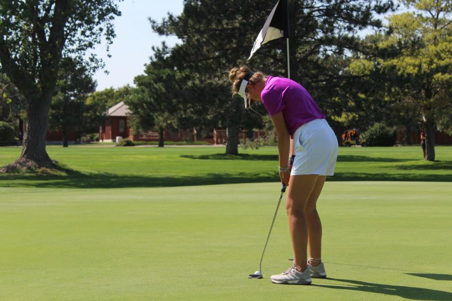 Junior Gracie Wente sinks a putt at the the Hays High Invitation Golf Tournament at Smoky Hill Country Club.