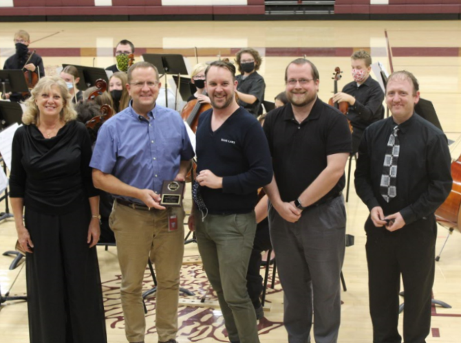 Orchestra+director+Joan+Crull%2C+principal+Martin+Straub%2C+vocal+director+Alex+Underwood%2C+band+director+Matthew+Rome+and+assistant+orchestra+director+Nathan+Mark+pose+in+front+of+the+Concert+Orchestra+after+awarding+Straub+with+his+KMEA+Honor+Administrator+of+the+Year+plaque+at+the+Fall+Orchestra+Concert+that+was+held+on+Oct.+13+in+Gym+A.