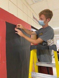 Junior Ryan Schuckman decorates the junior hallway.
