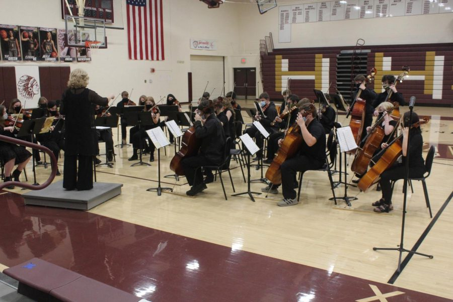 Joan Crull leads the orchestra at their winter concert.