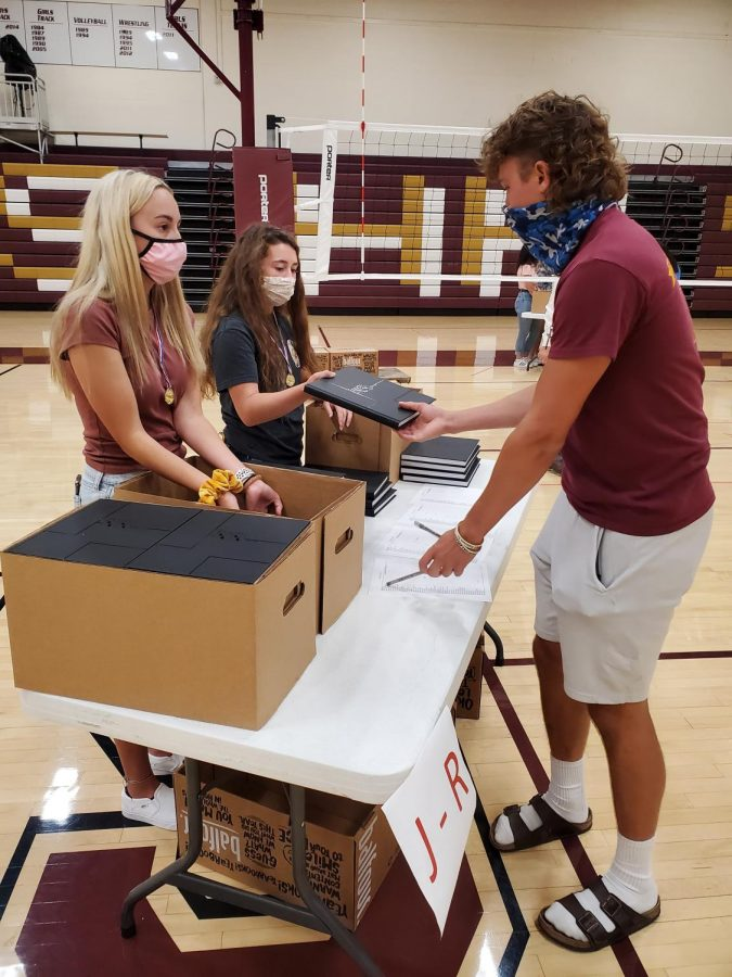 Leah Legleiter hands a yearbook to senior Miles Keller during yearbook distribution this year. The yearbook received the Kansas Scholastic Press Association's All Kansas Award.