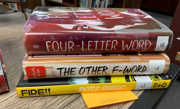 The Library is holding a poetry contest. The categories are Blackout poetry and Spine poetry. This is one example of Spine poetry. It reads: Four-Letter Word,      The Other F-Word:    Fire!!