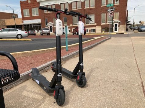 The electric scooters are usually parked on a sidewalk near a bike rack. They should be parked facing the street and out of the way of pedestrians and traffic.