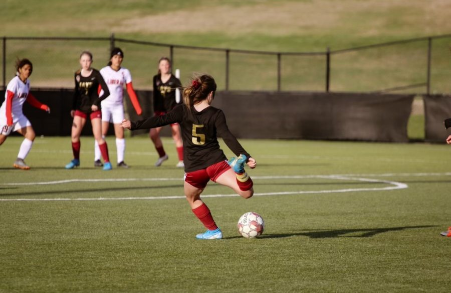 Senior Maggie Robben kicks the ball while playing against Liberal on April 22. Soccer has been one of the many sports affected by cancellations.