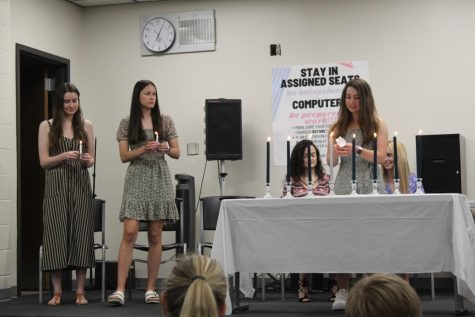 Junior Leah Legleiter lights a candle at the Quill and Scroll International Honorary Society ceremony.