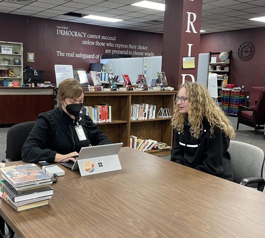 Junior Kaley Rajewski has her library card looked up and updates information with Holly Ray from the Hays Public Library.