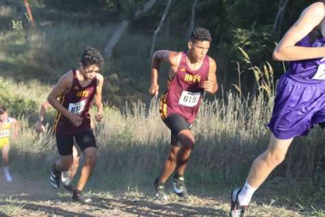 Senior Matthew Dempsey (left) follows behind sophomore Ty Dempsey while running up a hill.