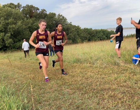 Sophomore Brynn Kinderknecht (left) and junior Nayeli Cisneros (right) run next to each other as they near the finish line.