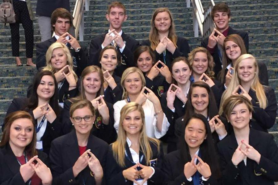 Students pose, holding up the DECA symbol as they represent Kansas at the International Career Development Conference.