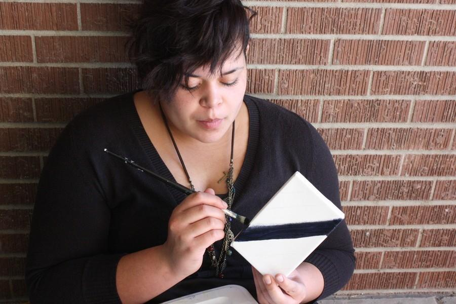 Art student paints on small canvas.