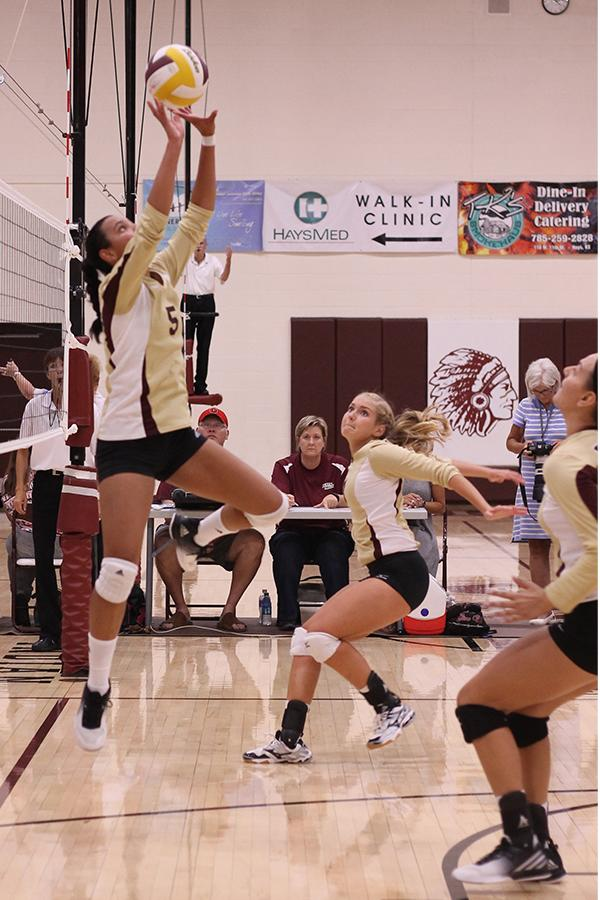 Freshman Tasiah Nunnery sets up sophomore Jaysa Wichers for a kill attempt on Aug. 30 in the HHS gym.