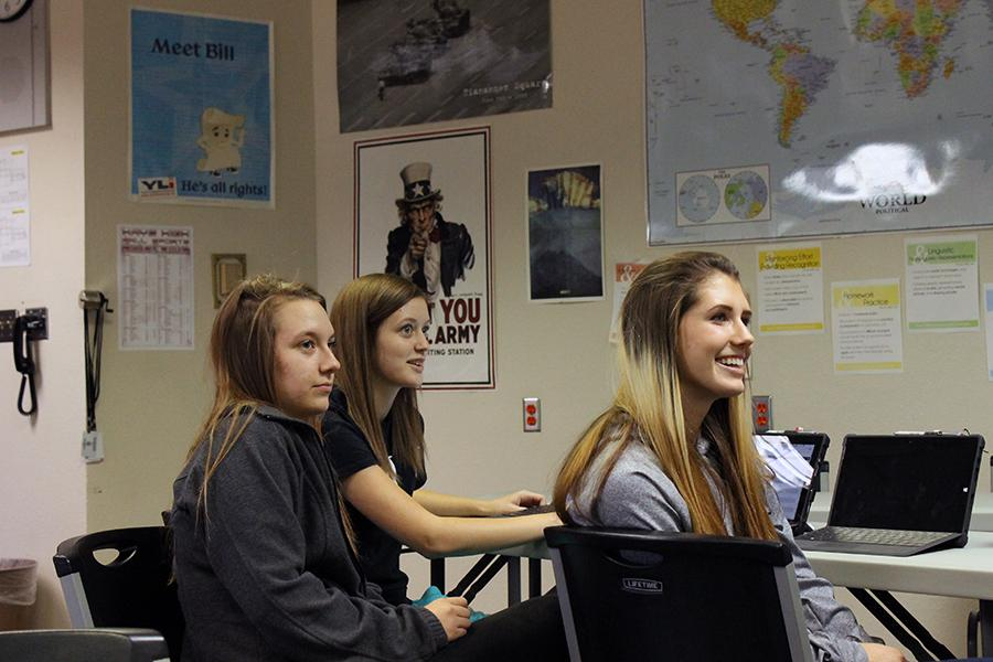 Seniors Raina Basso, Cassy Quinby and Courtney Molleker present their issue ad to the class.