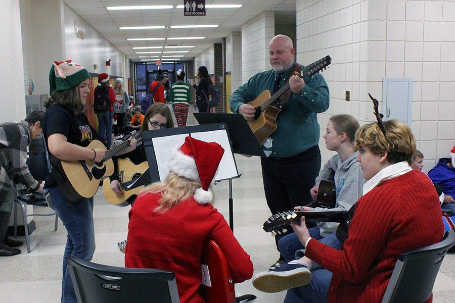 The guitar club performs in the freshman hallway before first hour.