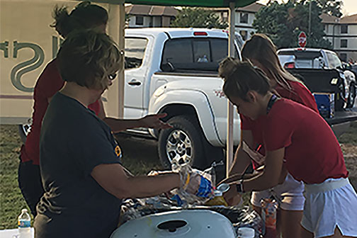 Astra Bank employees serve food at tailgate.