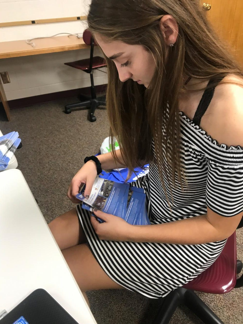 Junior Kallie Leiker counts out 30 coupon books for each of the DECA members. Each student is asked to sell their share, and those turned back in will go to the local McDonald's for them to sell.