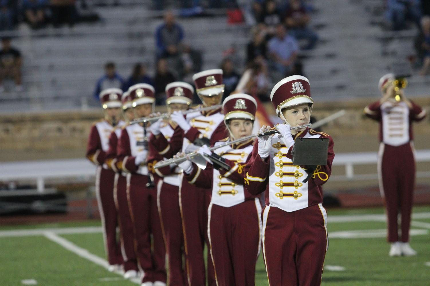 The marching band plays during a football game during halftime. Two students took first chair during district band.