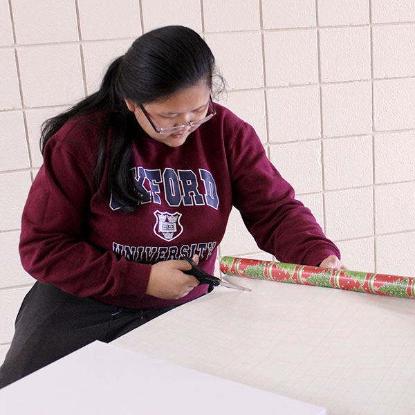 Senior Lucy Lin cuts wrapping paper.
