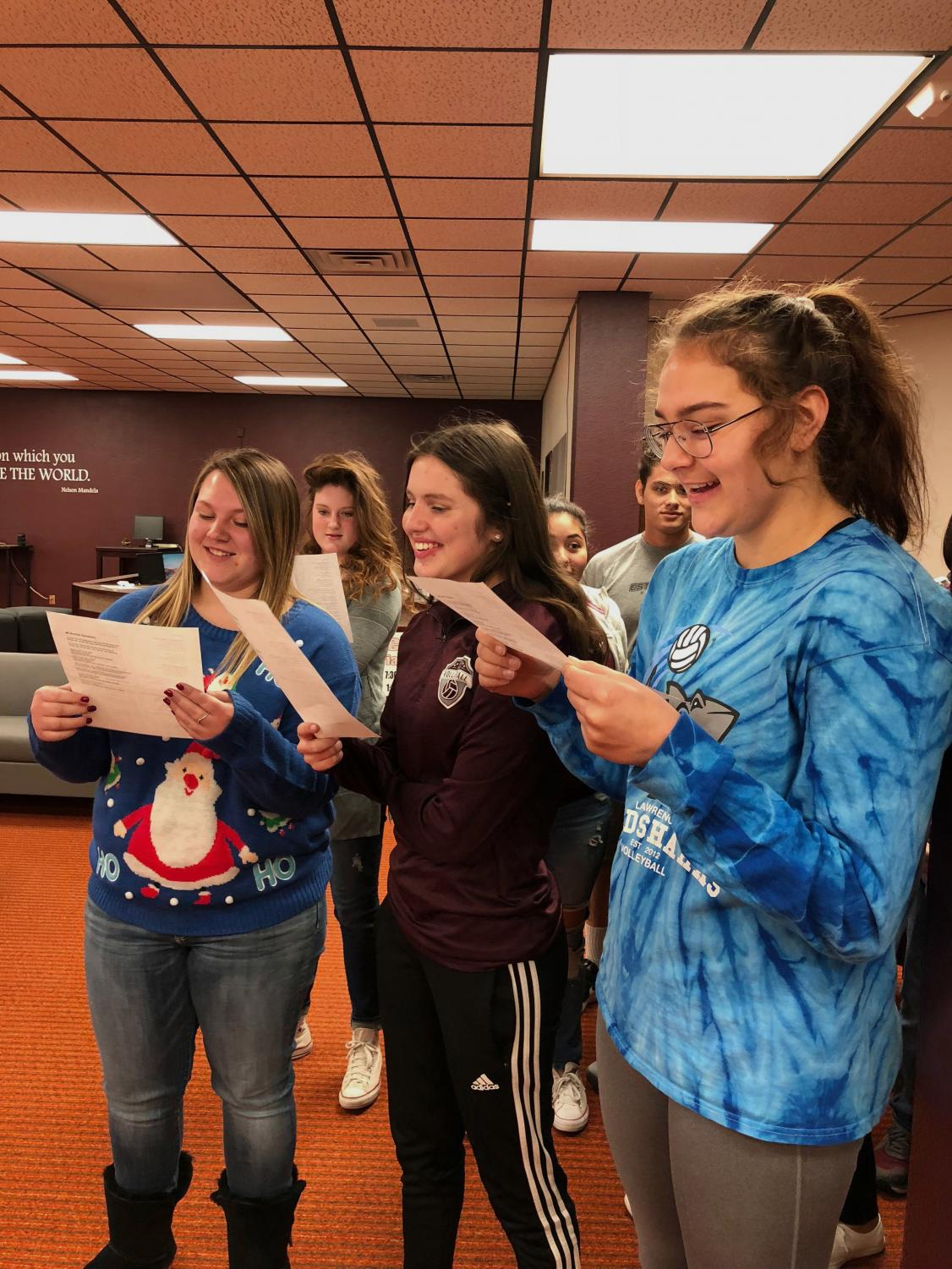 Juniors Lindsey Pfannenstiel, Hannah McGuire and Jaysa Wichers carol in the library during G2. This is their second year caroling.