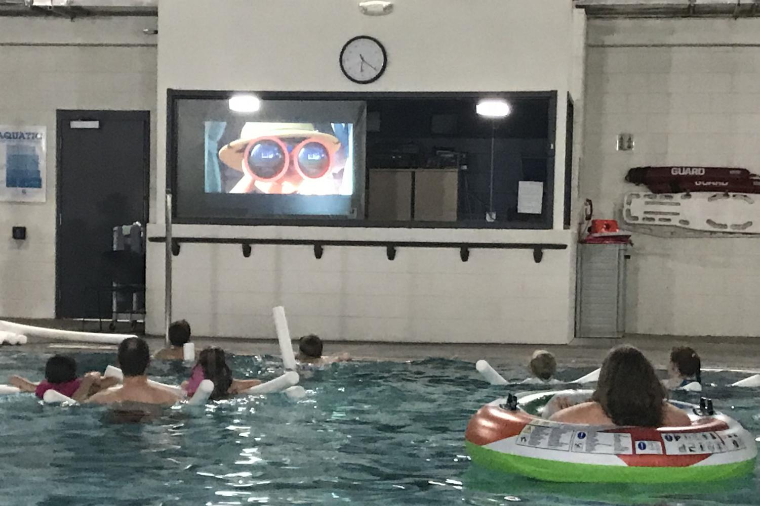 The public attends the movie while enjoying the comfort of a pool.