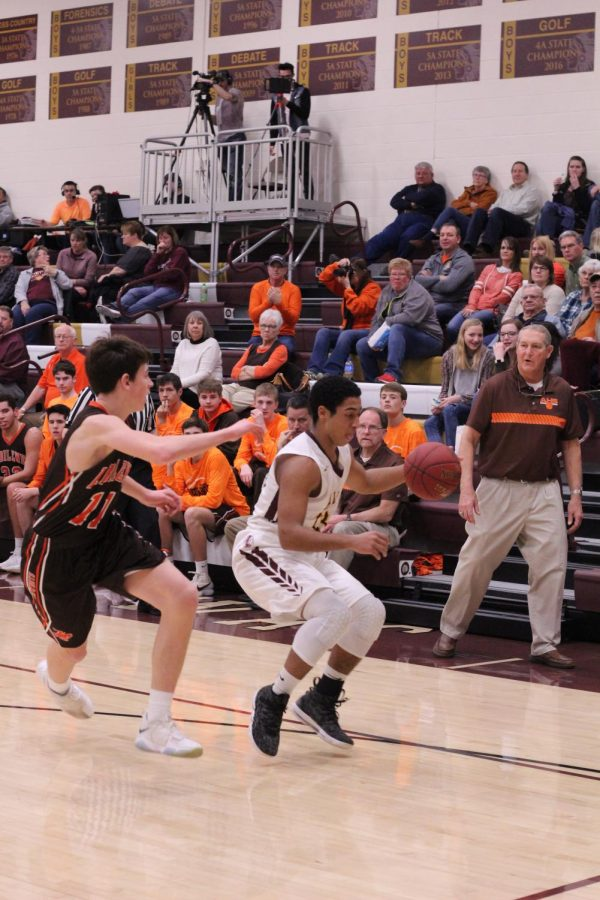 Junior Trey McCrae dribbles to the baseline and comes to  a jump stop while being guarded closely  by an Abilene defender.