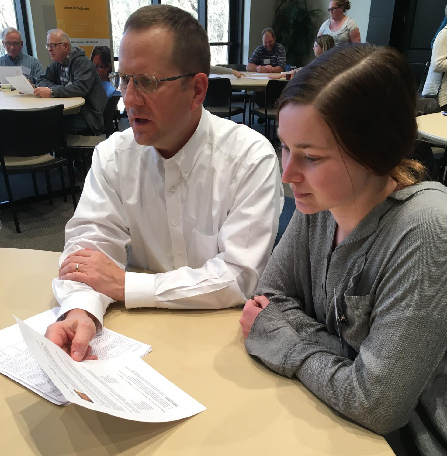 Senior Lisa Schoenberger and Principal Martin Straub look over the handout for the Neighborhood Project. The project was put together by a committee with the intent to bring together members of our community.
