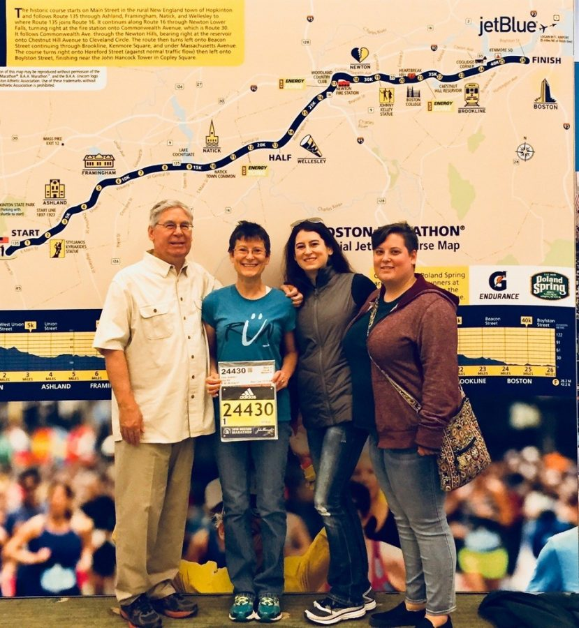 Instructor Andrea Zody poses  with her family and her race bib. Zody finished her first  Boston Marathon on April 16.