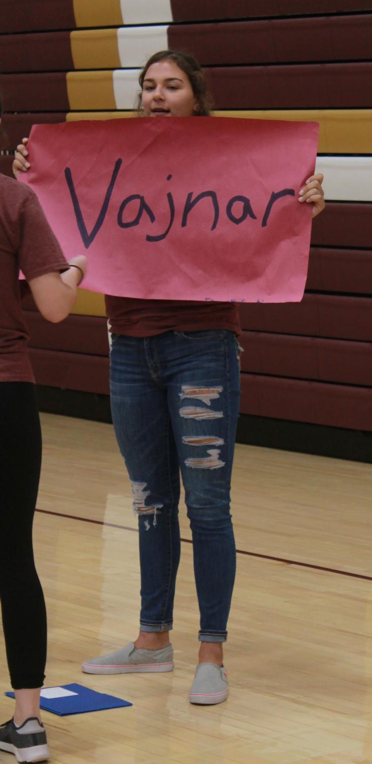 Senior Jaysa Wichers holds up a sign with her assigned academy to help the freshmen in her group find her.