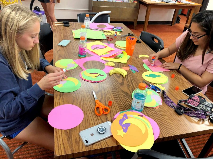 Students+Claire+Shippy+and+Cristina+Leos+work+on+Homecoming+decorations.