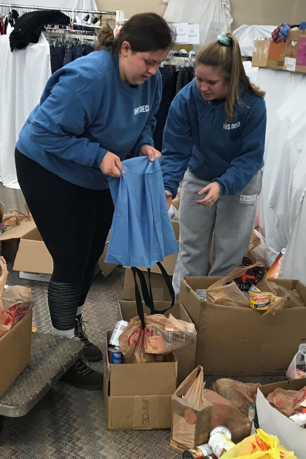 Senior Shyann Schumacher and junior Cassidy Prough set cans down to be counted and sorted. This is Schumacher's second year helping and Prough's first year.