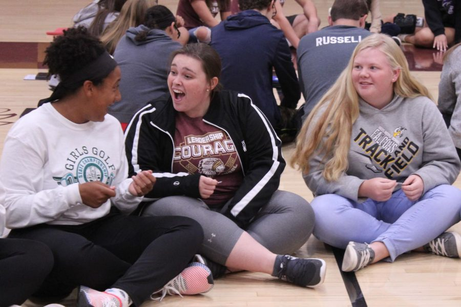 Freshman Taleia McCrae, senior Hannah Harman and freshman Katie Tinkel participate in the Wright Family Activity. The object of the activity was to move a paper clip left and right every time they heard