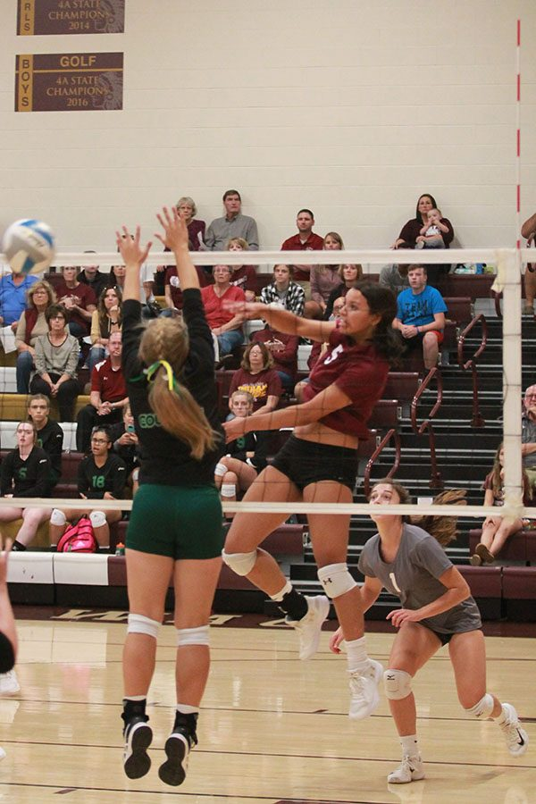At+the+recent+home+game+against+Salina+South%2C+Tasiah+Nunnery+is+making+a+kill+between+two+blockers.+