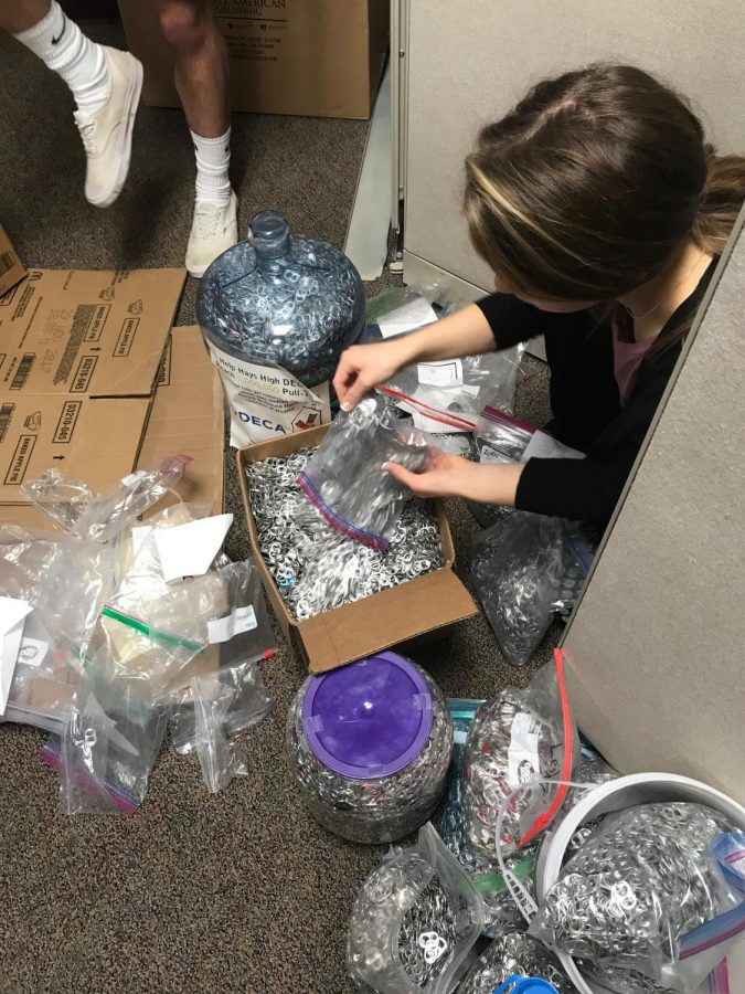 Senior Isabelle Braun sorts pull tabs that were collected from the middle school contest.