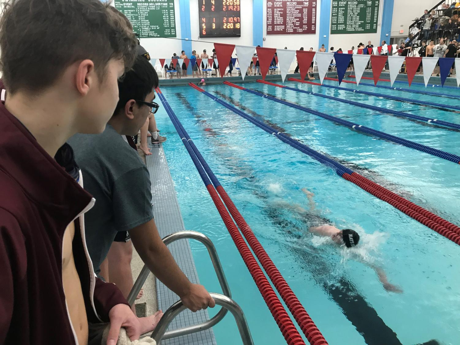 Hays swimmers watch as senior Brett Bowles completes his last 50 yards in the 200 Individual Medley.