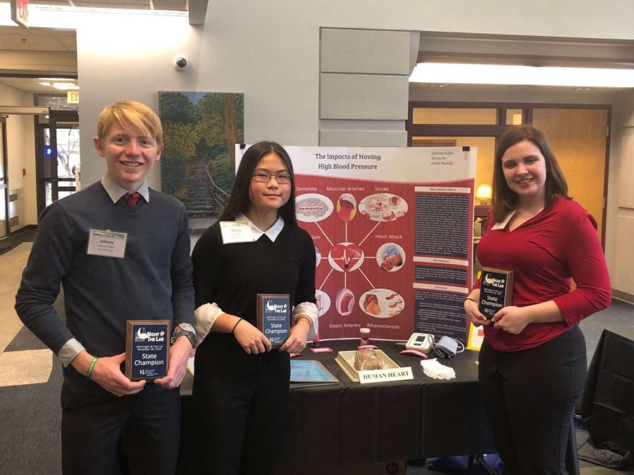 Senior Johnny Fuller and sophomores Ginny Ke and Callie Raacke with their project and award. The three will now have their presentation displayed during the Kansas Idea Network of Biomedical Research Excellence (K-INBRE) Symposium.