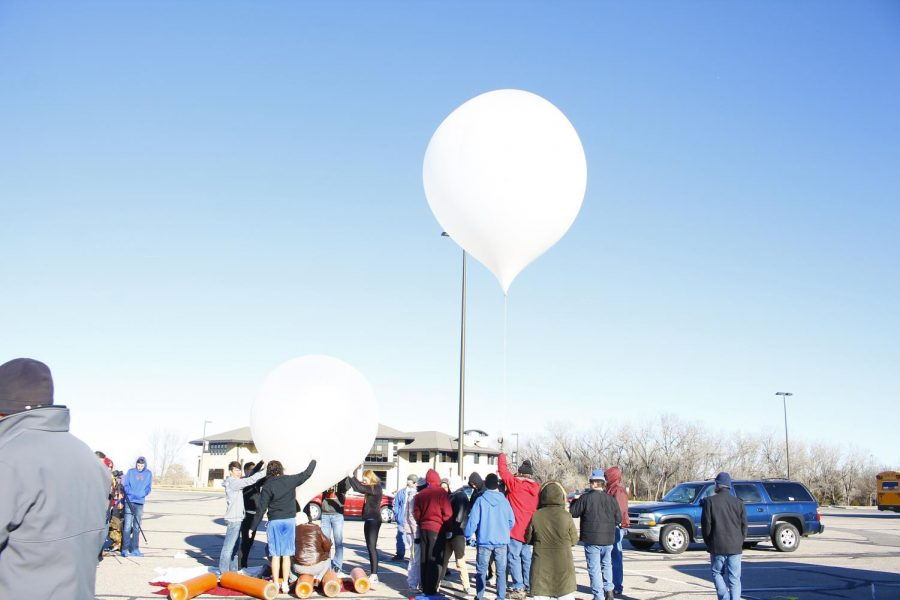Several students from Hays High and other schools that participated help fill the balloons with helium. After they filled up the balloon, they carefully let it up into the air.
