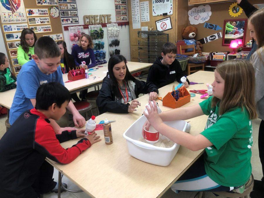 Junior Peyton Niernberger helps fourth grade students make snowmen crafts.
