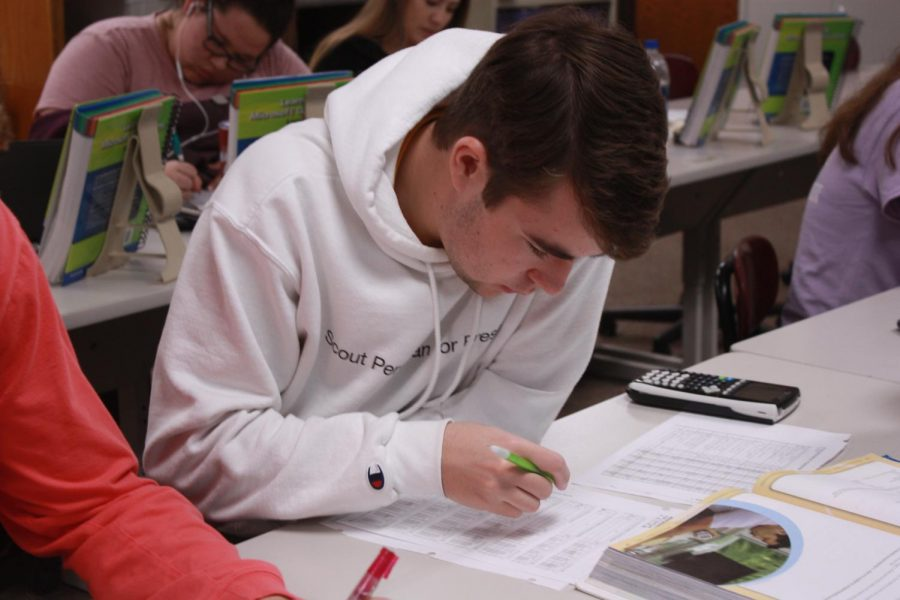 Senior Cameron Karlin works posting information from his ledger to his accounts during work time in his accounting class.